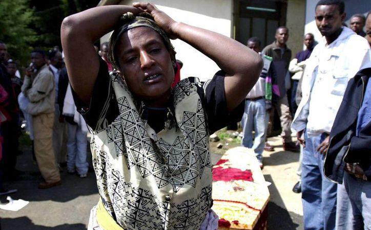 Una mujer muestra su desconsuelo junto al ataúd de su padre cerca del depósito de cadáveres de Melenik en Adis Abeba (Etiopia). El hombre murió al abrir fuego la policía etíope sobre un grupo de manifestantes. (EFE/Archivo)