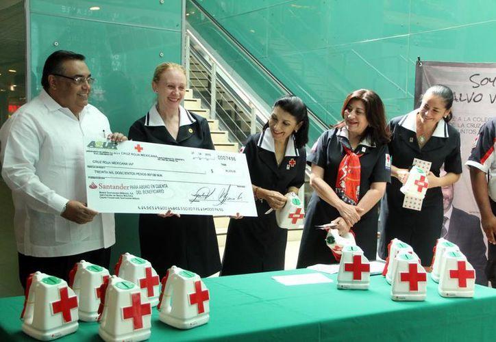 Momento de la entrega del cheque por 30 mil pesos de Grupo Asur a la Cruz Roja de Yucatán. (José Acosta/SIPSE)