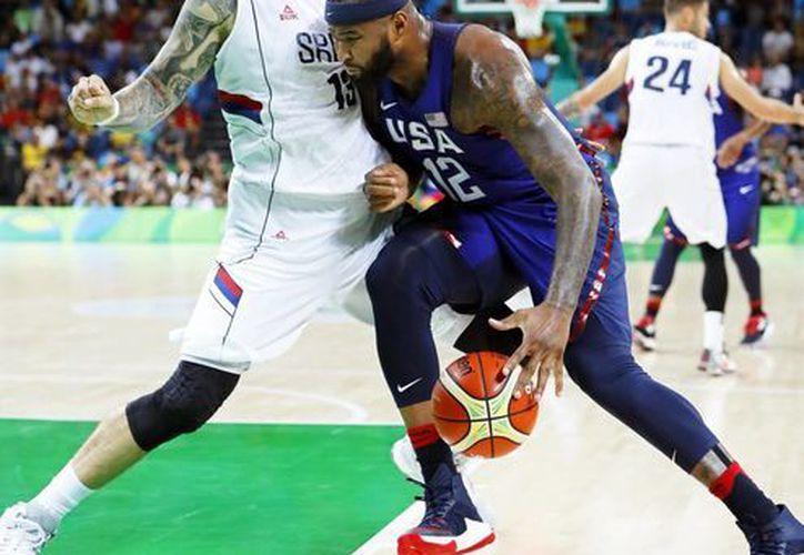 DeMarcus Cousins (derecha) de EE.UU. defiende un balón ante el serbio Miroslav, durante la final de baloncesto disputada este domingo, en Río 2016. (EFE)