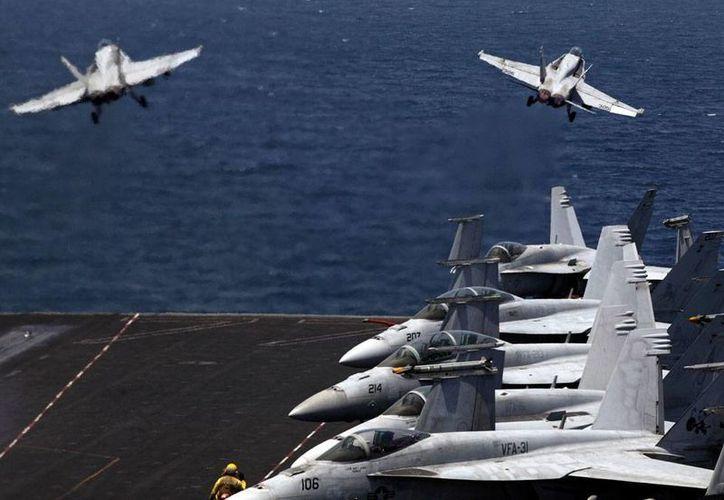 Aviones-caza F-18 de Estados Unidos toman vuelo con rumbo a Irak, desde le portaaviones George H. W. Bush, anclado en el Golfo Pérsico, en un 'episodio' más de una interminable guerra. (AP)