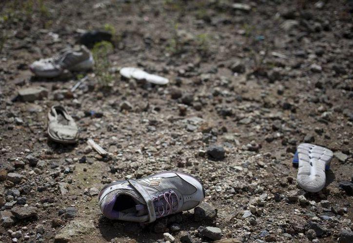 Imagen de varios zapatos abandonados cerca del lugar donde un deslave golpeó el vecindario El Cambray en 2015, en Santa Catarina Pinula, en las afueras de la ciudad de Guatemala. (AP/Moisés Castillo)