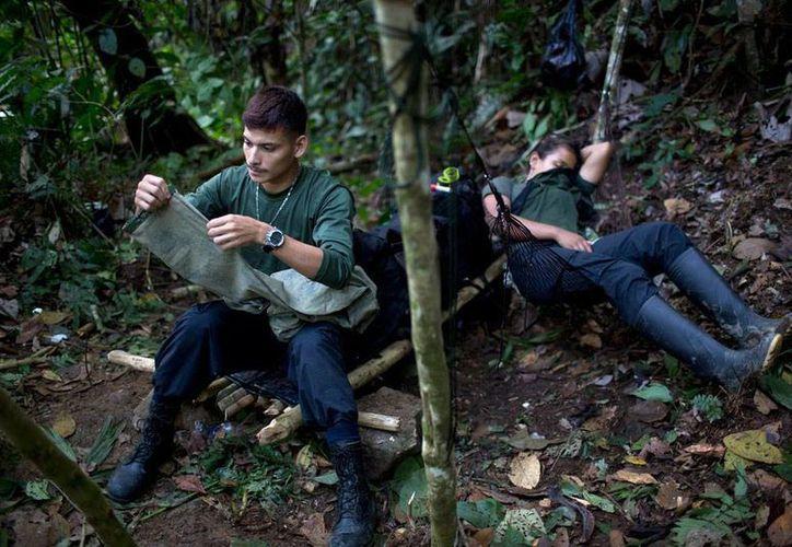 Un soldado del Frente 36 de las FARC arregla un pantalón mientras su compañera Gisell descansa en una hamaca, en un campamento cerca de Antioquia, Colombia. Esta guerrilla y el Gobierno se acercan a un acuerdo de paz definitivo. (Foto: AP/Rodrigo Abd)