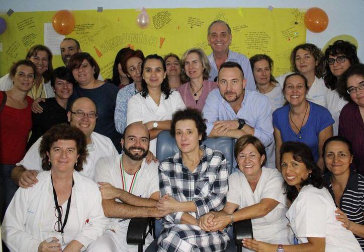 La auxiliar de enfermería Teresa Romero (c) posa junto a sus compañeros y su marido, Javier Limón (3ºd), tras ser trasladada a una habitación del Hospital Carlos III. (EFE)