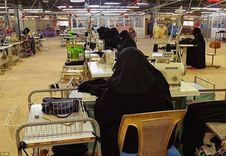 Mujeres confeccionan niqabs, trajes que cubren de los pies a la cabeza dejando solo los ojos a la vista, vestimenta que son obligadas a usar en los territorios controlados por el EI. (Agencias)