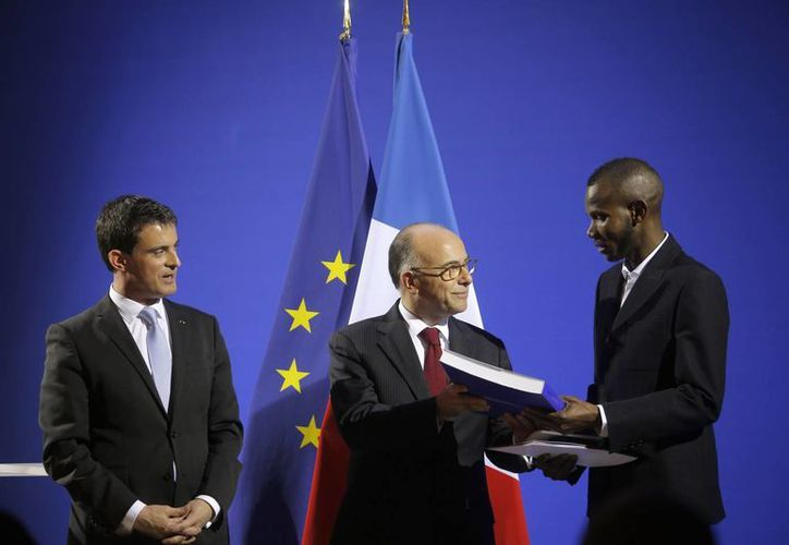 Primer ministro francés Manuel Valls, izquierda, y el ministro del Interior, Bernard Cazeneuve, centro, otorgan la ciudadanía a Lassana Bathily en una ceremonia en París. (Agencias)