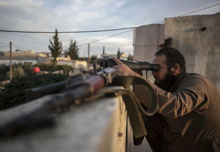 Un rebelde sirio observa fuertes comabtes en una zona rural de la provincia de Idib, Siria. (Agencias)