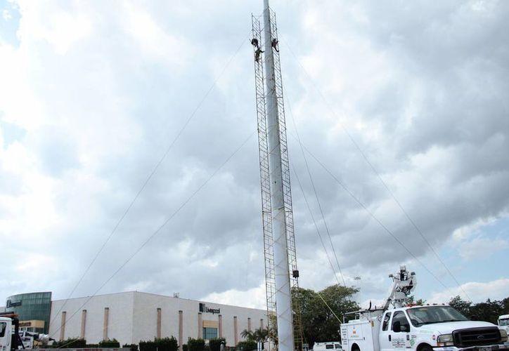 La nueva bandera con que contará Mérida al norte de la ciudad pesa el doble que la anterior, es decir, la nueva pesa 120 kilos. En la foto, preparativos antes de su colocación. (Jorge Acosta/SIPSE)