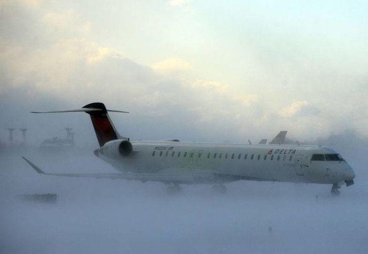 La intensa nevada en el norte de Estados Unidos ha desquiciado, entre otras actividades, la transportación. En la imagen, un avión intenta tomar pista, en medio de la nieve, en el aeropuerto internacional de Buffalo, Nueva York. (AP)