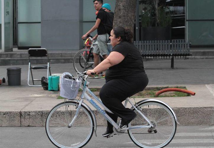 El objetivo del nutriólogo es enseñar al paciente a comer bien y evitar alimentos que causen obesidad. Imagen de una mujer ciclista con sobrepeso en la Ciudad de México. (Notimex)