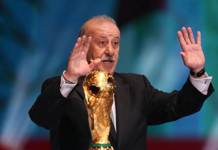 Vicente del Bosque entrega la Copa del Mundo durante el sorteo del Mundial en Costa do Sauipe, Bahia (Brasil).