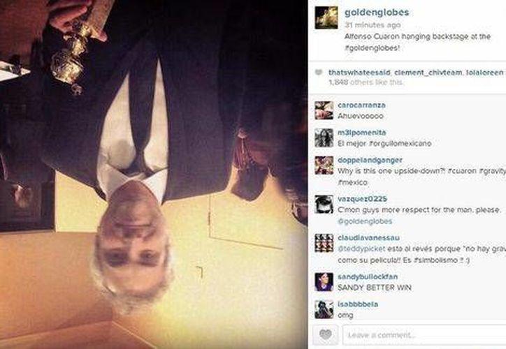 """De cabeza, Alfonso Cuarón presume su galardón tras ganar como mejor director por """"Gravedad"""". La foto está de cabeza en alusión a la película. (Instagram Goldenglobes)"""