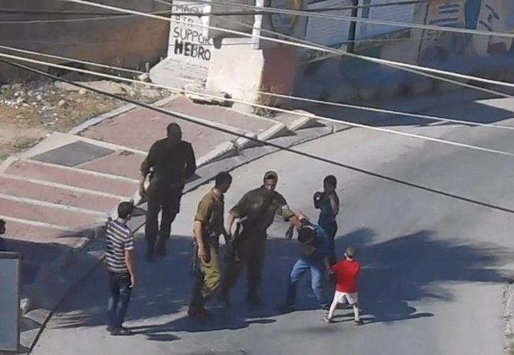 El efectivo le dio una patada en la pierna al chico, mientras otro se alejó de la escena. (Captura de pantalla)