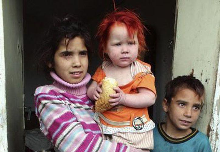 Los hijos de Sasha y Atanas Ruseva permanecen en la entrada de su casa de Nikolaevo, Bulgaria. (EFE)