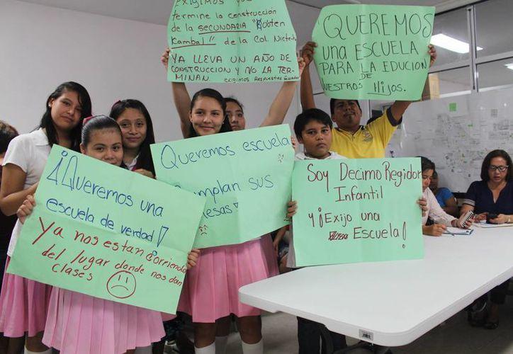 Estudiantes se presentaron con pancartas en las oficinas de la SEyC para pedir regresar a tomar clases a su secundaria, que se encuentra en obra.  (Luis Ballesteros/SIPSE)