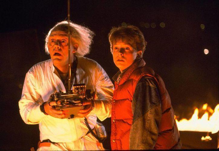 Michael J. Fox (d) y Christopher Lloyd protagonizaron la exitosa trilogía de ciencia ficción, que el próximo año cumplirá 30 años desde su estreno. (Universal Pictures)