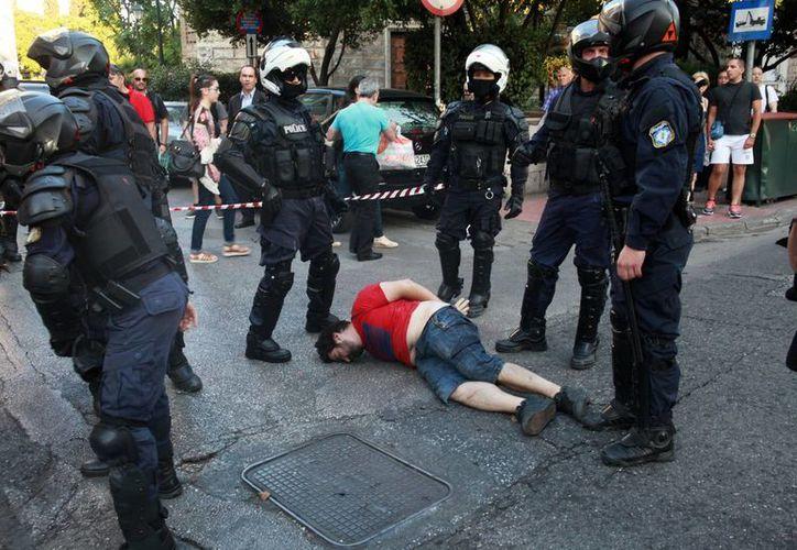 La policía antidisturbios detiene a un manifestante antes de un mitin organizado en el Grecia. (Agencias)