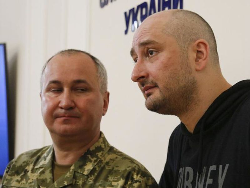 Russian journalist Arkady Babchenko, center, speaks to the media.
