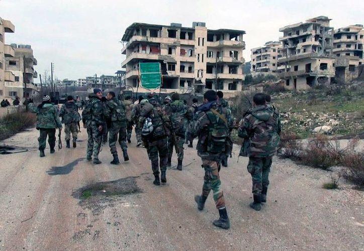 Foto del 12 de enero de 2016,de la agencia oficial SANA que muestra a soldados sirios y de la milicia aliada patrullando la ciudad de Salma en la provincia Latakia, Siria. (AP)