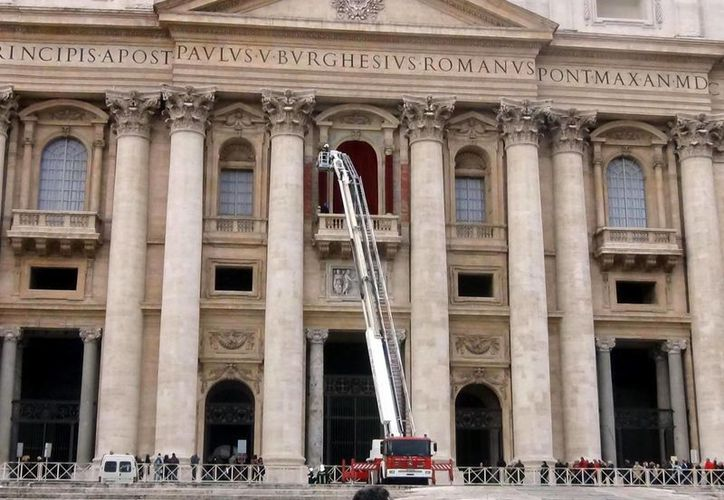 Bomberos decoran con terciopelo rojo el balcón central de la Basílica de San Pedro, en la Ciudad del Vaticano, hoy. (EFE)