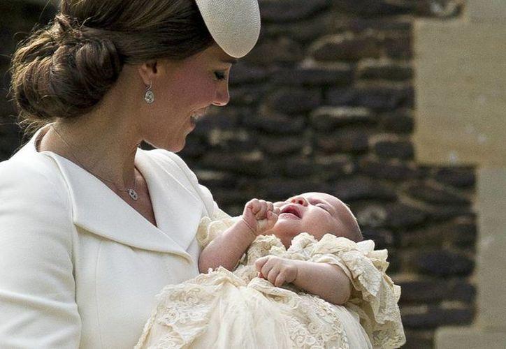 La duquesa Catalina de Cambridge sostiene a su hija Carlota momento antes de ingresar a la ceremonia de bautizo, a la cual acudieron solamente 21 invitados. (AP)