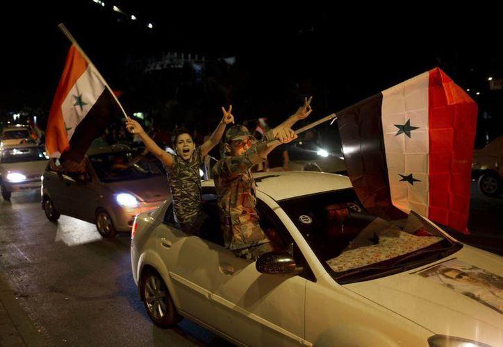Simpatizantes del régimen de Bashar al Assad celebran la reelección del mandatario en las calles de Damasco. (AP)