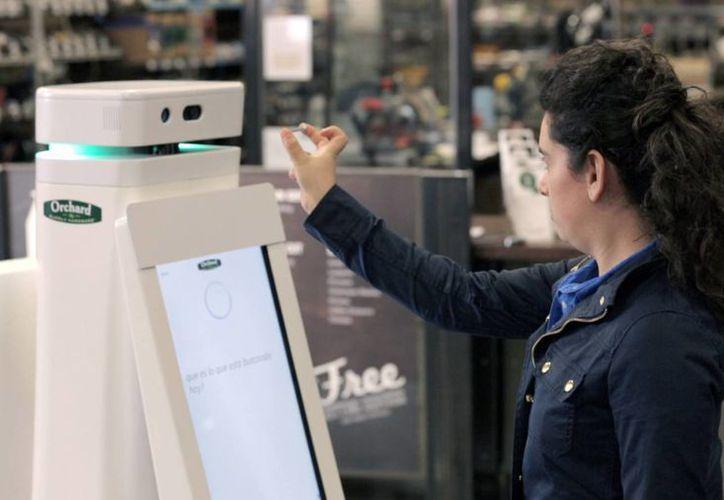 En esta foto sin fecha suministrada por Lowe's, una mujer sostiene un clavo frente a la cámara de un robot OSHbot para que le ayude a localizar otro igual en un comercio. (Agencias)