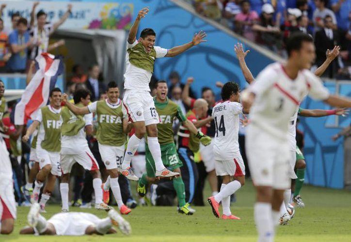 Los jugadores 'ticos' celebran su pase a los octavos de final, situación que levantó sospechas en la FIFA. (AP)