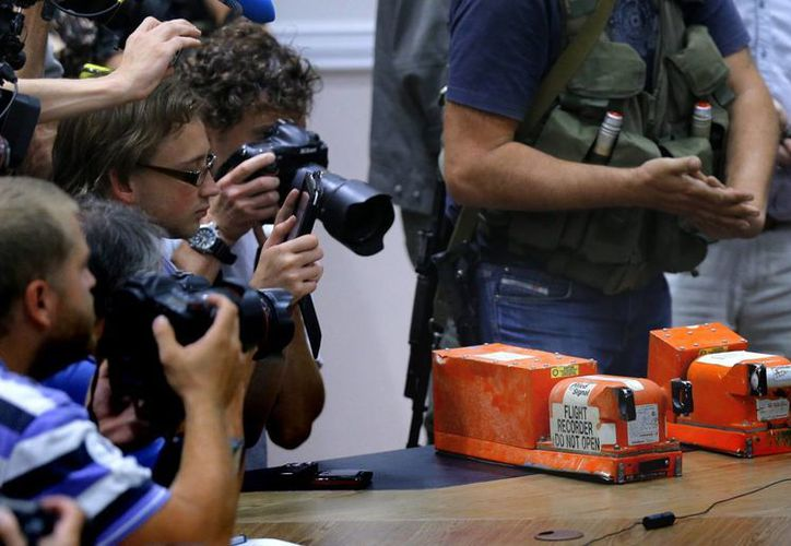 """Periodistas toman imágenes de las dos """"cajas negras"""" del vuelo MH17 de Malaysian Airlines antes de ser entregadas por separatistas prorrusos al coronel Mohamed Sakri (fuera de cuadro), el pasado lunes. (EFE)"""