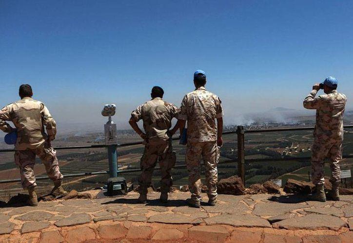Desde Los Altos del Golán -lugar en el que un militar de Israel cayó herido por balas perdidas de combates-, Cascos Azules de la ONU observan las columnas de humo de los enfrentamientos en Siria. (Efe)