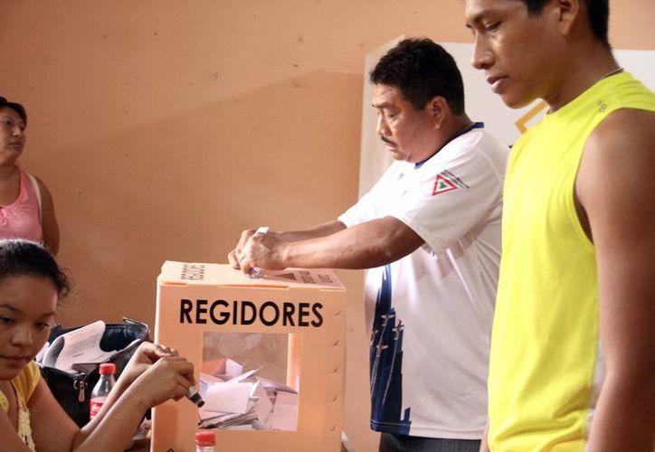 El Partido Revolucionario Institucional (PRI) ganó la mayoría de las comisarías de Mérida, incluidas las poblaciones que eran consideradas bastiones panistas, como Caucel (la más grande). Imagen de dos pobladores a la hora de depositar su voto en las urnas. (Milenio Novedades)