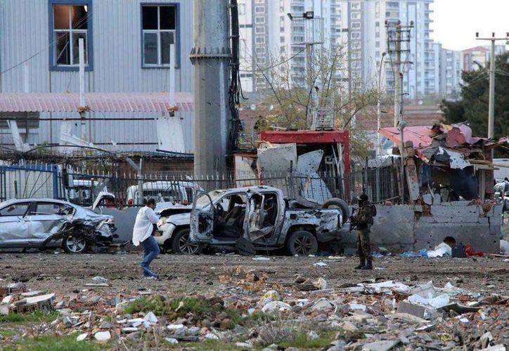 Funcionarios forenses y de seduridad trabajan en el sitio de la explosión de un coche-bomba contra policías en la ciudad turca de Diyarbakir, mayormente curda, el jueves, 31 de marzo del 2016. Los explosivos detonaron al paso de un vehículo que transportaba a fuerzas especiales de la policía, causando la muerte de al menos siete agentes. (AP)