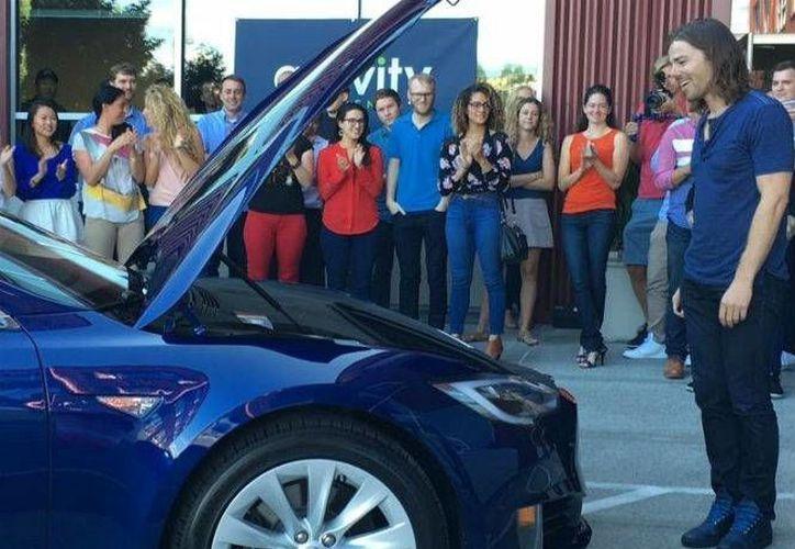 Dan Price, CEO de Gravity Payments, observa el auto Tesla que le regalaron sus empleados. (Facebook)