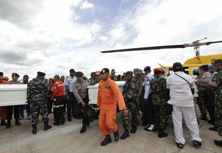 Personal militar y de los servicios de rescate portan los ataúdes con los restos mortales de las víctimas del accidente de un avión de carga a su llegada al aeropuerto de Mosos Kilagin en Timika, en la provincia de Papúa, Indonesia, el 1 de noviembre de 2016. (EFE)
