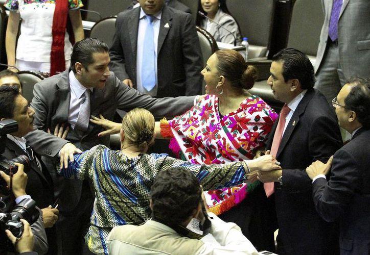 Los legisladores de PAN, Germán Pacheco y Enrique Aubry del Verde Ecologista, durante el pleito en la Cámara de Diputados. (Notimex)