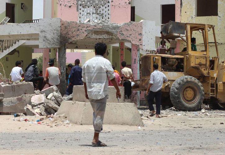 Personas reunidas en el sitio de un ataque suicida con un coche bomba en Adén, Yemen. (AP/Wael Qubady)