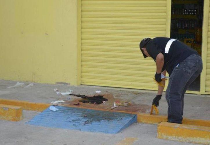 Un agente ministerial examina la sangre que quedó tras el crimen de la mujer en la colonia Plan de Ayala Sur, en julio del año pasado. (Archivo/SIPSE)