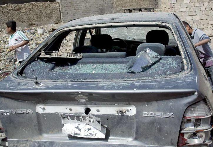 Ciudadanos iraquíes comprueban los daños en un vehículo tras un bombardeo en Irak. (EFE/Archivo)