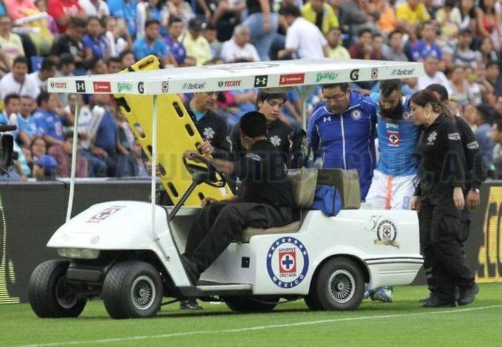 Imagen de Marc Crosas al ser sacado de la cancha, debido a la lesión que sufrió durante el partido contra el América. (twitter/@Cruz_Azul_FC.)