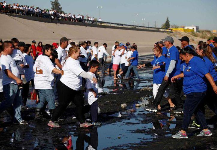 Al llegar la hora del encuentro, los asistentes se aproximaron caminando o corriendo entre el fango del lecho del río, mientras algunos gritaban, se abrazaban, se tomaban fotografías y lloraban. (Reuters)