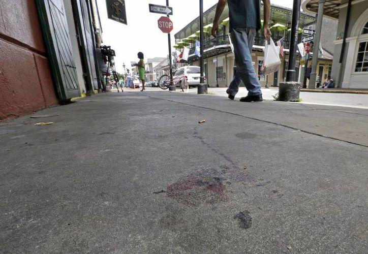 Manchas de sangre se aprecian en la acera de la calle Bourbon en Nueva Orleáns, donde ocurrió un tiroteo en la madrugada del domingo. (Foto de AP/Gerald Herbert)
