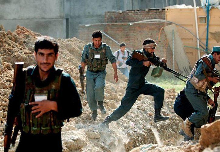 Fuerzas de seguridad de Afganistán se reorganizan durante los enfrentamientos con milicianos en Kabul, donde hoy los rebeldes intentaron tomar el aeropuerto. (AP)