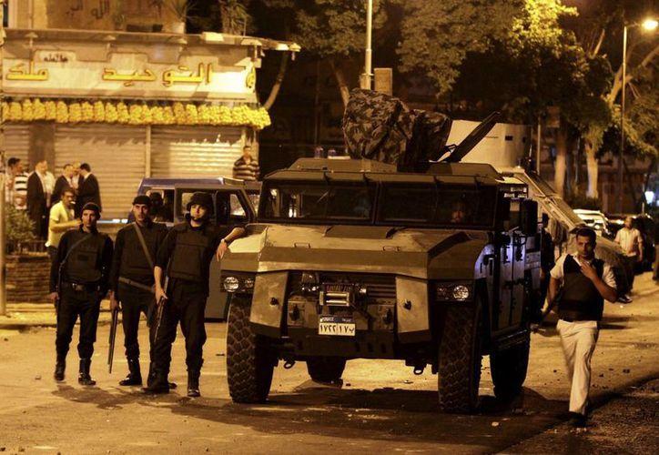 La policía antidisturbios se colocan cerca de un vehículo de la policía después de que hombres armados abrieran fuega contra varios agentes en la Universidad Al Azhar de El Cairo. (Agencias)