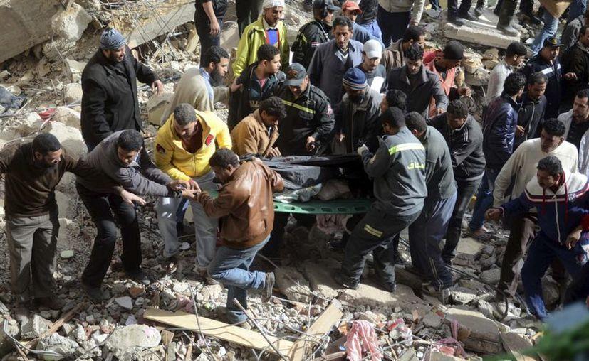 Servicios de emergencia transportan a una víctima tras el derrumbe hoy de un edificio residencial en Alejandría. (EFE)