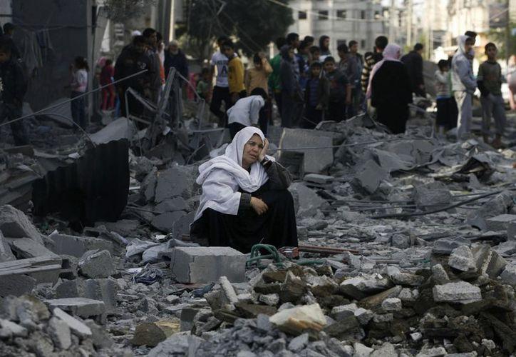 Una mujer palestina se encuentra entre los escombros tras un ataque aéreo israelí en el campamento de refugiados de Rafah, en el sur de la Franja de Gaza. (Agencias)