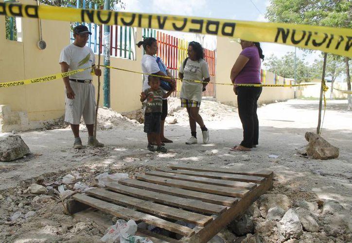 El cuerpo de agua fue tapado con unas maderas y tiene una cinta para evitar el paso. (Jesús Tijerina/SIPSE)