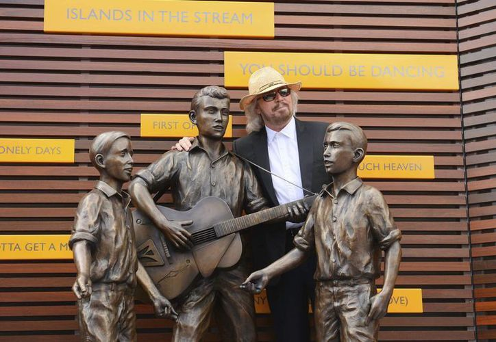 El músico australiano Barry Gibb posa junto a una estatua en honor de Barry, Robin y Maurice Gibbs, componentes del grupo musical Bee Gees, durante la inauguración oficial del Paseo de los Bee Gees en Australia. (EFE)