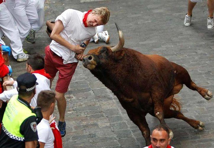 Momento en que un joven es embestido por uno de los astados en el encierro de este viernes en Pamplona. (AP)