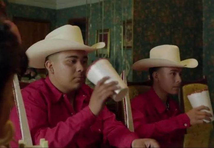 En el video se muestran actores con sombrero y bebiendo. (Captura de pantalla)