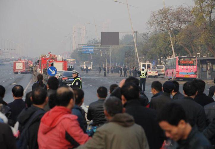 Un grupo de personas observa a la Policía mientras investiga una explosión ocurrida en 2013, que se registró a las afueras de la sede del Partido Comunista, en Taiyuan, provincia de Shanxi, China. (Archivo/EFE)