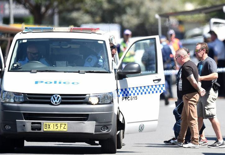 Un hombre esposado detenido por la policía en el escenario de un tiroteo en Sídney, Australia. (EFE)